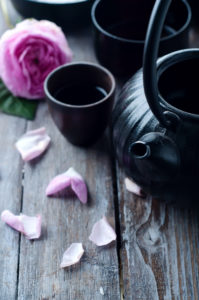 asian tea set and rose petals on the wooden background
